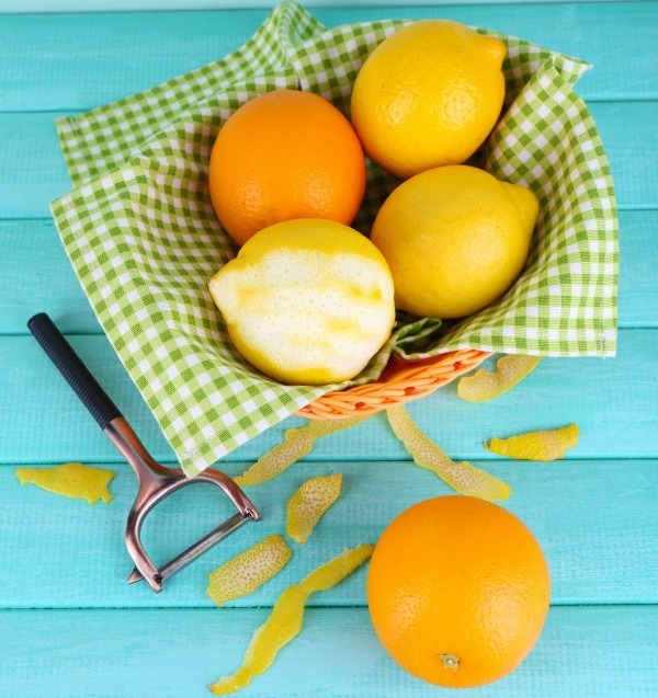 Lemons and oranges on napkin in basket and peeling knife on blue wooden background